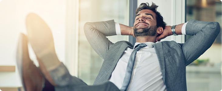 Man lounging at desk hands behind his head