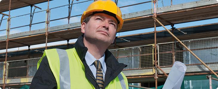 man in hard hat looking at site plans