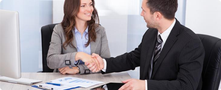 Businesswoman Looking At Businessman While Shaking Hand